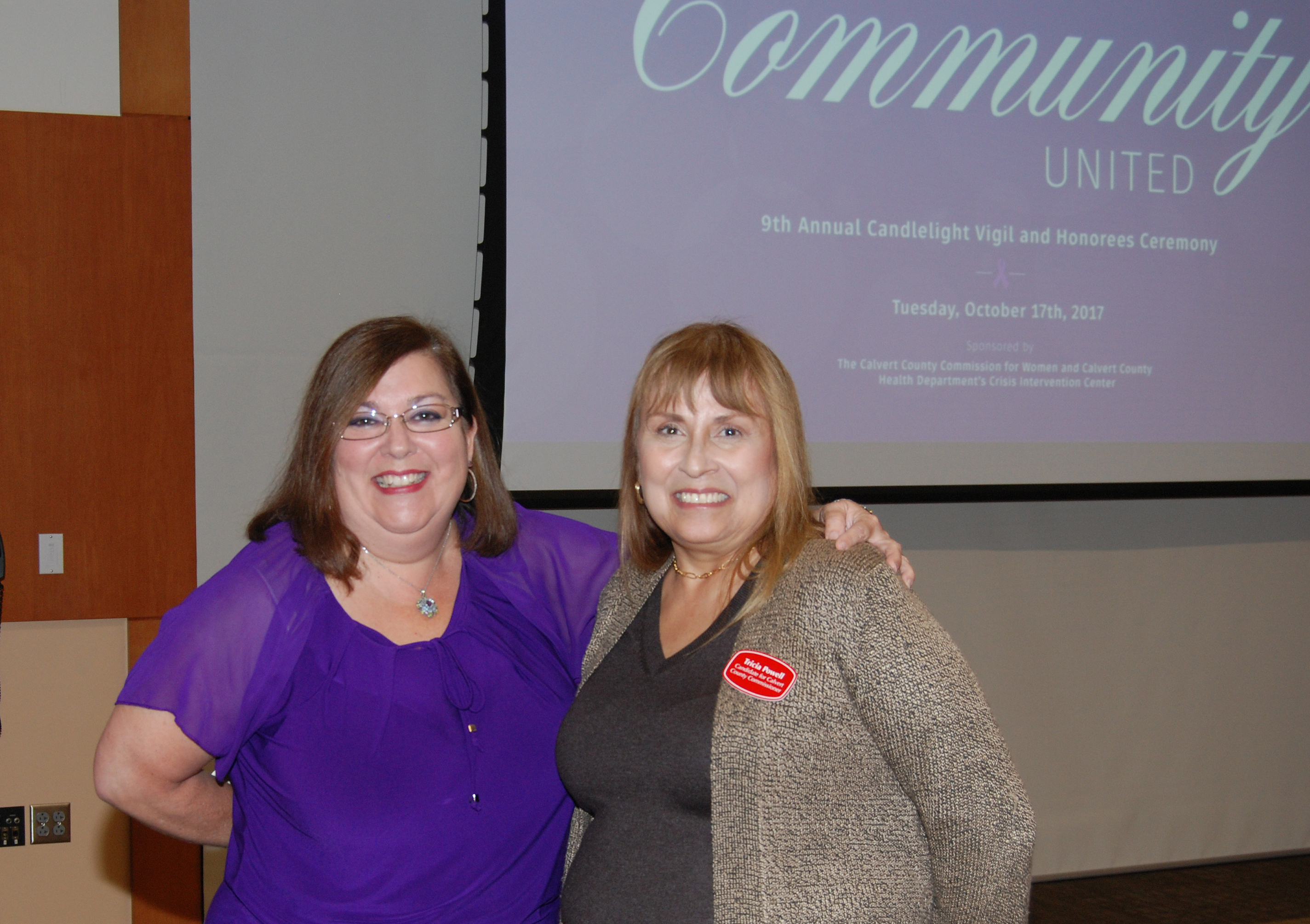 Two Women Smiling with Community United Presentation Behind Them on Screen