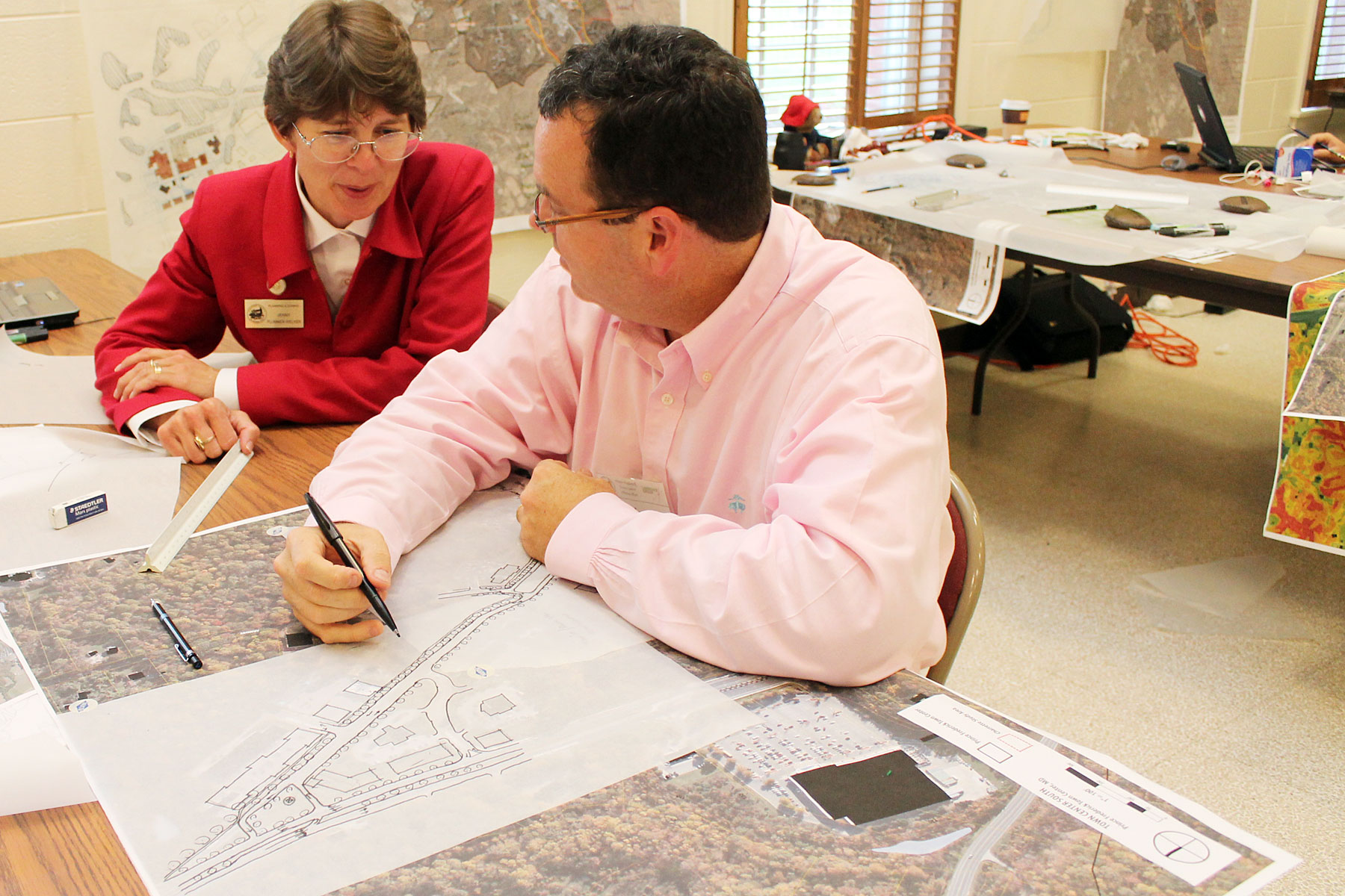 Jenny Plummer-Welker of Calvert County Community Planning and Building goes over maps and data with Wade Walker from the Lawrence Group during the charrette