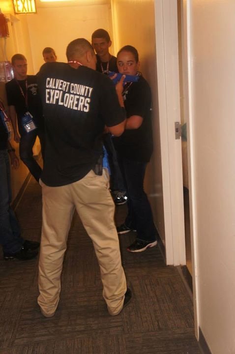 Explorers in doorway simulating police take down
