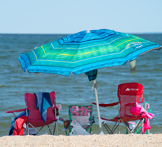 A pink child's beach chair sits in the sand between two red adult chairs under a blue beach umbre
