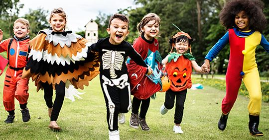Kids in Halloween costumes running outside toward viewer