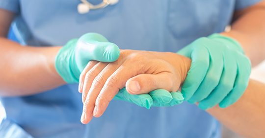 Healthcare professional with gloves holds a patient's hand