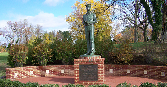 Bronze statue of a sailor on a red brick pedestal and patio surrounded by lush green grass, trees an