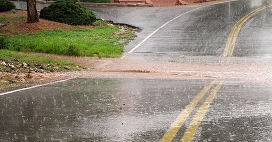 Drainage flooding a residential roadway during a rainstorm